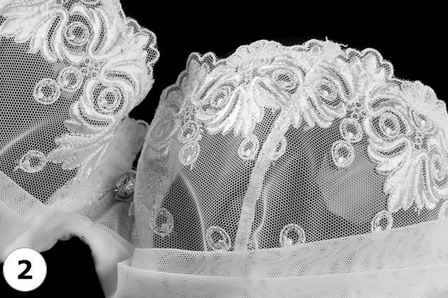 ホワイトが眩しい刺繍デザイン。中央ではチュールに包まれた大粒のラインストーンが静かに輝きます。