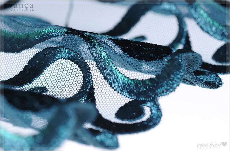 エメラルドグリーンの糸が織り込まれた高貴な輝きを持つレース。